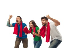 Drive in sport. Three soccer fans woman and men cheering for favourite sport team with bright emotions isolated on white studio background. Looking excited, supporting. Concept of sport, fun, support.