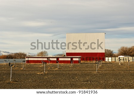 Drive-in theater with a bright white and red screen, dirt parking area, and speakers on posts just waiting for warmer weather