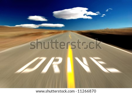 Drive sign on an empty high desert road with motion blur, Eastern Sierra Mountains, California