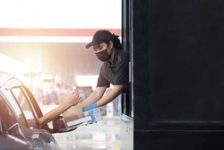 Drive through and takeaway for buy fast food for protect covid19. New normal life style. The staff woman wearing medical glove and mask and handed a food to customer. Drive thru and take away concept.