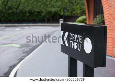 Drive thru sign with shop and road background. #500226739