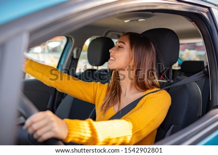 Driver adjusting the Rear Mirror looking at herself. Adjusting the rear view mirror. Woman adjusts the rear view mirror with her hand. Happy young woman driver looking adjusting rear view car mirror