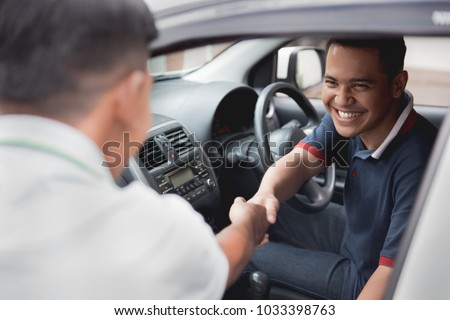 driver and friend or customer shake hand