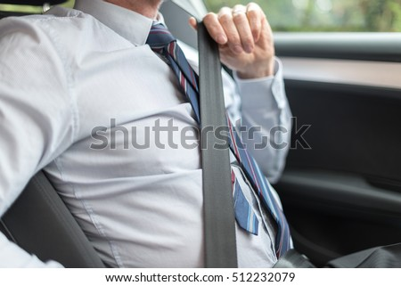 Driver fastening his seat belt before starting car