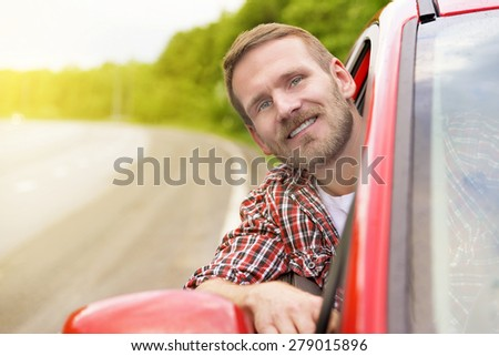 Driver. Happy smiling man in new red car on the road.