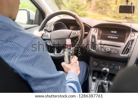 Driver holding bottle of alcohol while driving car #1286387761