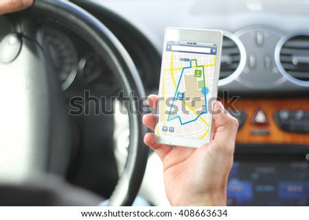 driver holding smartphone with gps app interface. All screen graphics are made up.
