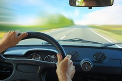 Driver in car holding steering wheel. Blurred road and sky