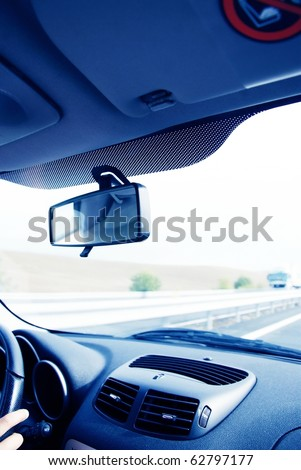 Driver in car holding steering wheel. Blurred road and sky-3