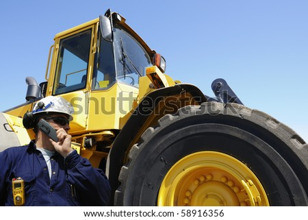 driver in hard-hat with large forklift, jcb, in background