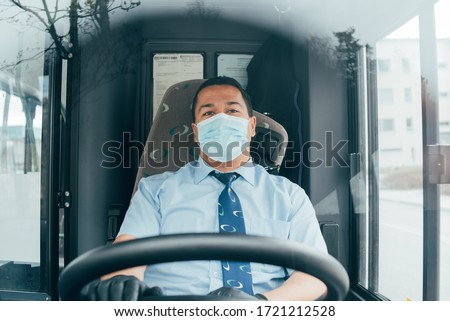 driver in mask looks at road while driving. young latin man bus driver in blue shirt has blue medical protection mask and black  gloves on hands.  bus driver wants to prevent  infection of covid 19.