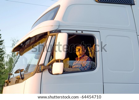 Driver in the cabin of his white truck in the evening