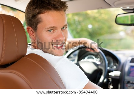 Driver is sitting in his car or van and is driving - he is looking back - stock photo
