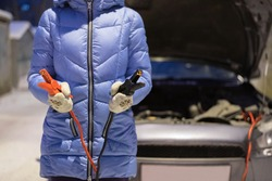 Driver is standing with a car jumper cables on the frozen car background.