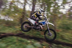 Driver jumping with enduro motocross motorcycle in forest
