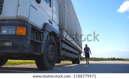 Driver opens the door and exits from parked truck. Man is walking near the lorry. Lorry parked in the countryside. Beautiful landscape at background. Bottom view Slow motion Close up.
