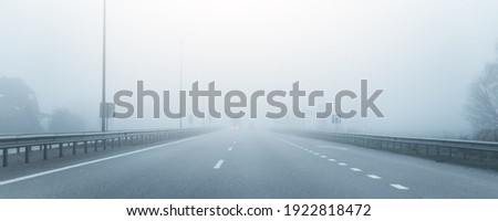 Driver POV on almost empty blue foggy misty rainy highway intercity road with low poor visibility on cold spring autumn morning. Seasonal bad rainy weather accident danger warning. car fog light Foto stock ©