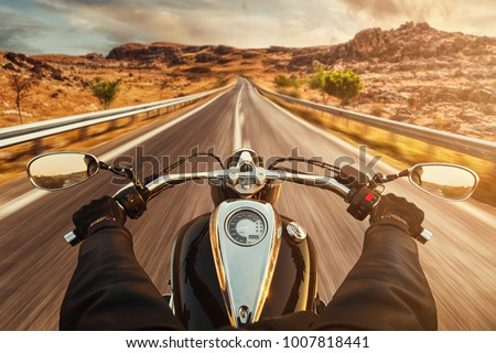 Driver riding motorcycle on an empty asphalt road #1007818441