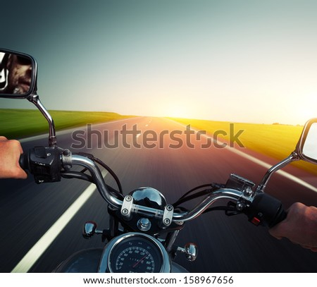 Driver riding motorcycle on an empty asphalt road