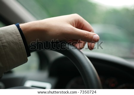 Driver's hand on steering wheel. Shallow DOF. - stock photo