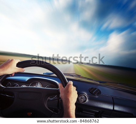 Driver's hands on a steering wheel and blurred road