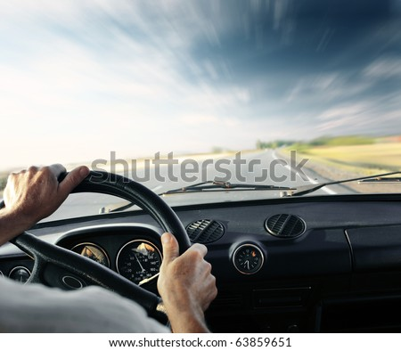 Driver's hands on a steering wheel of a car and blue sky with blurred clouds - stock photo