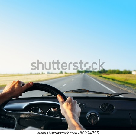 Driver's hands on a steering wheel of a retro car during riding on an empty asphalt road #80224795