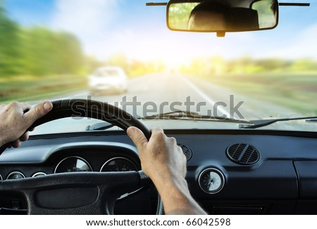 Driver's hands on steering wheel inside of a car