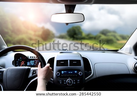 Driver\'s hands on the steering wheel inside of a car