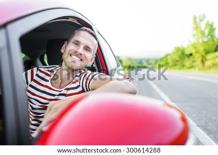 Driver. Smiling man in red car on the road at sunset.