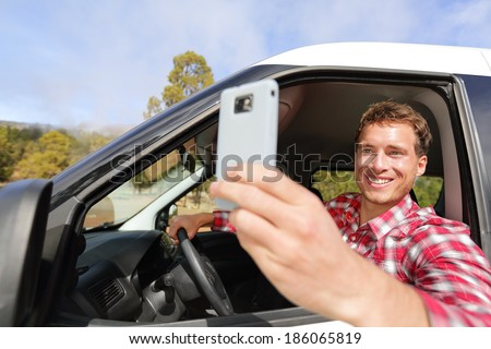 Driver taking photo with camera smartphone driving in car. Happy man taking picture with smart phone camera out window of car during travel road trip. Young Caucasian male model in his 20s.