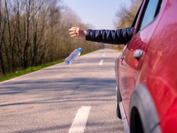 Driver throwing away plastic waste from car window on the road rear view