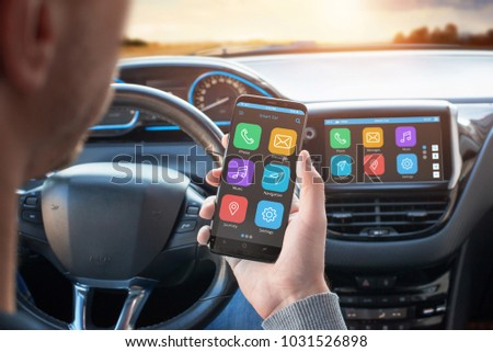 Driver uses a mobile phone with smart driving assistance apps. The app is connected to a car computer and is displayed on the board display. #1031526898