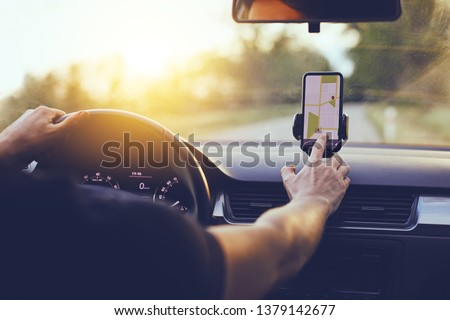 Driver using GPS navigation in mobile phone while driving car at sunset #1379142677