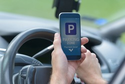 Driver using smartphone app to pay for parking in the paid parking zone in a city