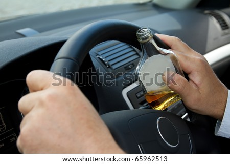 Driver with a bottle of alcohol sits behind the steering wheel