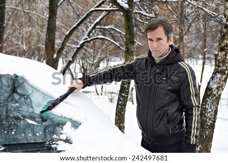 Driver with a brush cleans the car from the snow in the winter