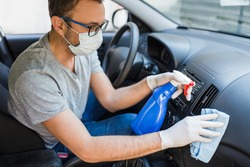 Driver with face surgical mask using disinfectant and microfiber cloth to clean car interior.