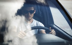 Driver. Young man in sunglasses sitting at the wheel of a car
