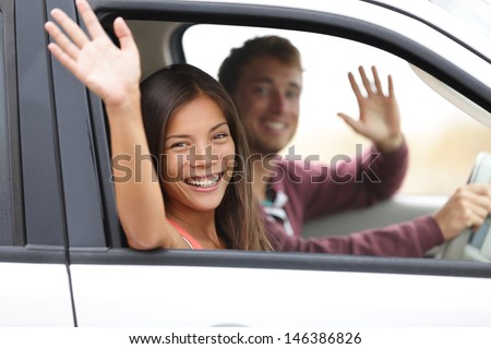 Drivers driving in car waving happy at camera Young couple on road trip in new car Interracial happy couple
