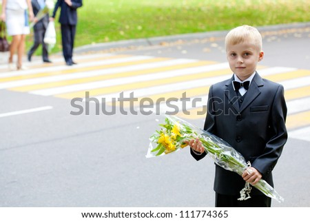 Drivers - please! September 1 children go to school. Schoolboy with flowers against the background of zebra crossing
