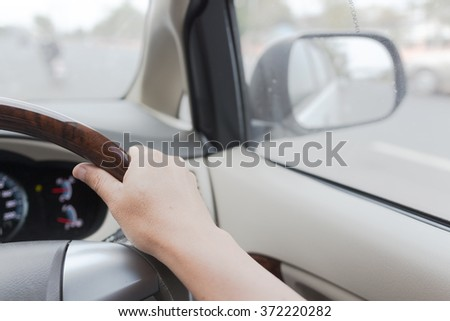 Drivers's hands on a stearing wheel of a car #372220282