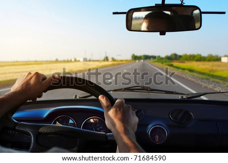 Drivers's hands on a steering wheel of a car