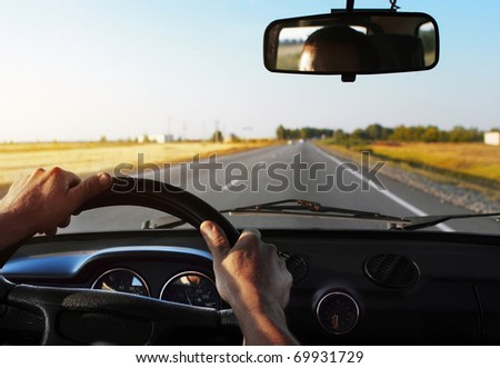 Drivers's hands on stearing wheel of a car