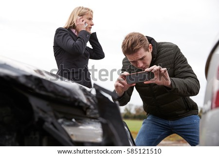 Drivers Taking Photo Of Car Accident On Mobile Phones