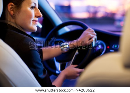 Driving a car at night - pretty, young woman driving her modern car at night in a city (shallow DOF; color toned image) - stock photo