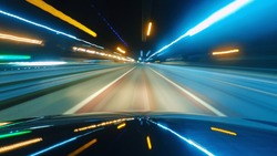Driving a car in the city at night. The camera on the hood of the car. Hyperlapse in the evening in the center of the city on the highway. Abstract soft glowing lines.