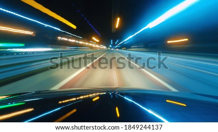 Photo of  Driving a car in the city at night. The camera on the hood of the car. Hyperlapse in the evening in the center of the city on the highway. Abstract soft glowing lines.