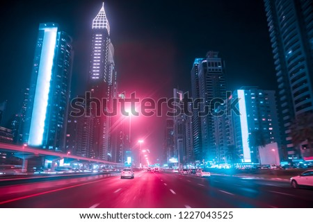 Driving a car on Sheikh Zayed Rd in Dubai at night, United Arab Emirates. Blurred motion. Duotone retro wave neon noir lights color toned