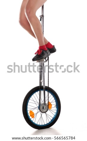 driving a unicycle on a white...
